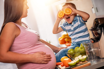 Mother and her kid making fresh orange juice in kitchen