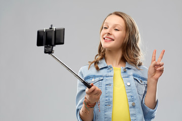 technology and people concept - happy smiling teenage girl taking picture by smartphone on selfie stick and showing peace over grey background