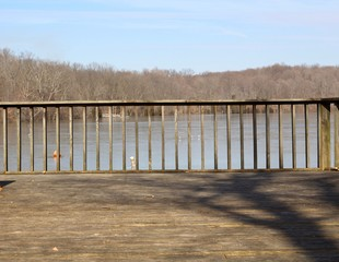 A view of the lake though the railings of the wood deck.