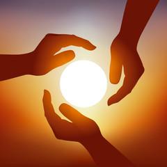 Concept de l'économie d'énergie avec trois mains qui protègent symboliquement le soleil pour privilégier les énergies renouvelables.