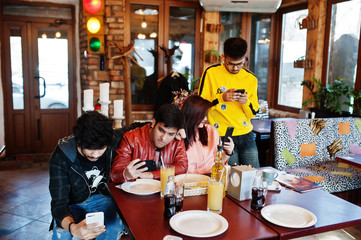 Group of asian friends sitting cafe. Happy indian people having fun together, sitting on couch and looking at mobile phones.