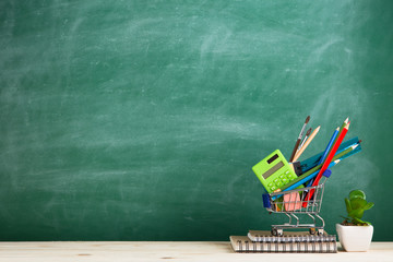 Education concept - school supplies in a shopping cart on the desk in the auditorium, blackboard background