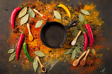 Herbs and spices selection (turmeric, paprika, Bay leaf, salt, chili pepper) and small black pan on dark rustic background, top view