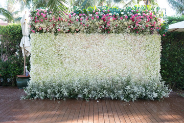 Wedding backdrop decorated with flowers on wooden ground