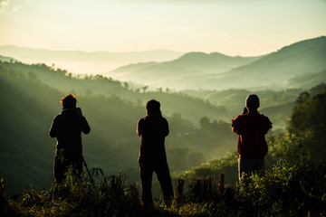 Silhouette of three photographers taking landscape pictures of morning mist on the mountain