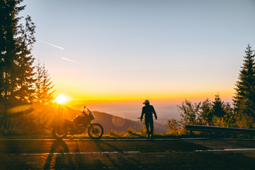 Silhouette of man biker and adventure motorcycle on the road with sunset light background. Top of mountains, tourism motorbike, vacation active lifestyle. Transfagarasan, Romania. Fototapete