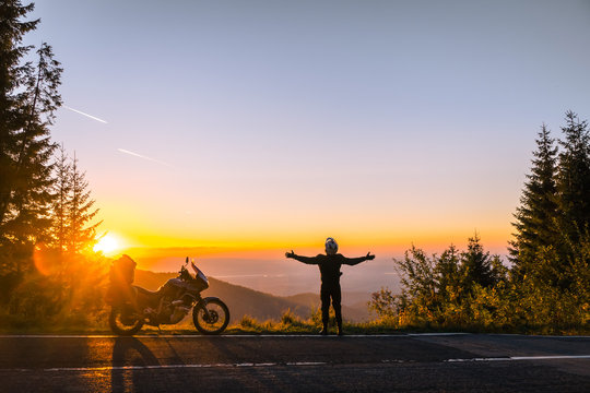 Silhouette of man biker and adventure motorcycle on the road with sunset light. Hands up. enjoy momment. Top of mountains, tourism motorbike, vacation active lifestyle. Transfagarasan, Romania.