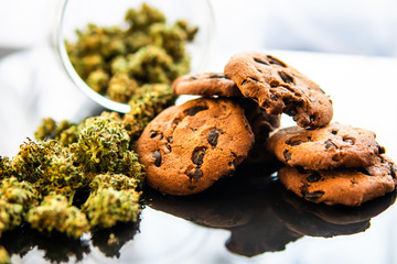 Concept of cooking with cannabis herb CBD. Cookies with cannabis and buds of marijuana on the table. Treatment of medical marijuana for use in food, black background.