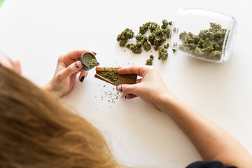 Woman rolling a marijuana blunt on white background. Close up of marijuana blunt with grinder. Cannabis use concept. Woman preparing and rolling marijuana cannabis joint.