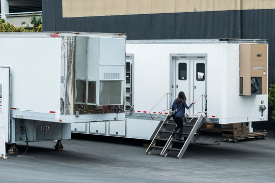 Woman walking up a stair into her trailer in media studio area