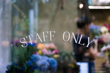 Staff only sign on window with blurry background of florist working in floral shop Wall mural