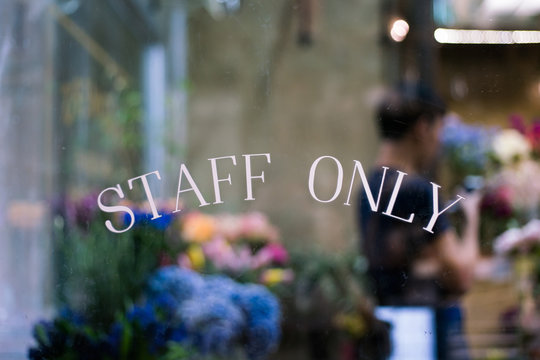 Staff only sign on window with blurry background of florist working in floral shop