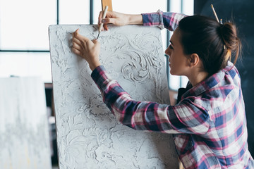 Plaster texture artwork. Woman painter with carving tool. Canvas on easel. Artist talent, creativity and imagination.