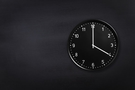 Black wall clock showing four o'clock on black chalkboard background. Office clock showing 4am or 4pm on black texture