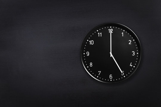 Black wall clock showing five o'clock on black chalkboard background. Office clock showing 5am or 5pm on black texture