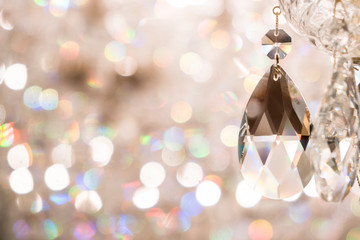 Close up image of crystal on chandelier with bokeh background