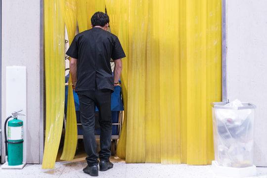 Staff pushing a cart through a plastic air curtain