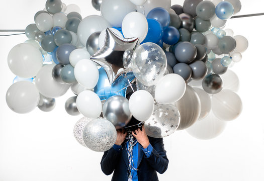 Handsome happy man with big bunch of balloons. Bearded man with balloons at birthday party. Stylish birthday guy holds air balloons. Happy businessman with helium balloons. Happy birthday concept.
