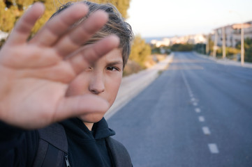 Teenager boy hiding his face with hand on empty asphalt road