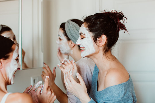 .Group of friends applying a revitalizing white mask on their faces. Beauty treatment, skin care, natural, spa and fun moments. Lifestyle.