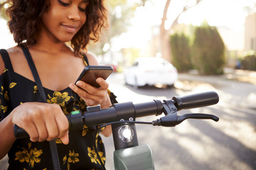 Millennial black woman standing on an electric scooter using smartphone,close up