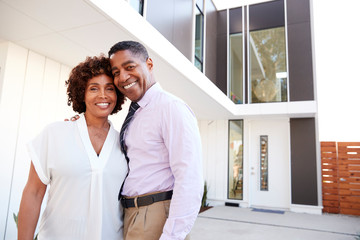 Middle aged black couple stand outside admiring their modern home, back view Wall mural