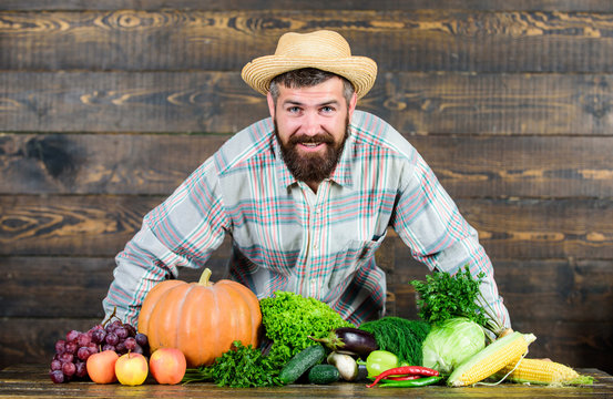 Man bearded farmer with vegetables rustic style background. Buy vegetables local farm. Locally grown crops concept. Local market. Homegrown vegetables. Farm market harvest festival. Sell vegetables