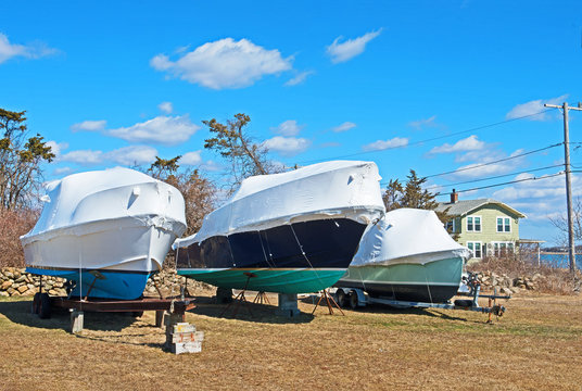 Three boats are stored for the winter in Fairhaven, Massachusetts, out of the water and on blocks with shrinkwrap style covers to protect them from the elements.