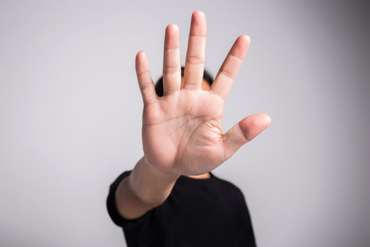 Hand of young man implying NO sign, rejecting expression or prevention