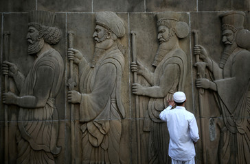 A man touches the wall of a Parsi fire temple featuring huge carvings of ancient priests on the occasion of the Persian New Year in Mumbai