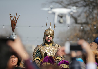 People take pictures as a reveller rides a horse during a parade as part of Navruz celebrations, an ancient holiday marking the spring equinox, in Almaty