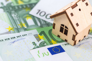 wooden symbol house with euro banknotes