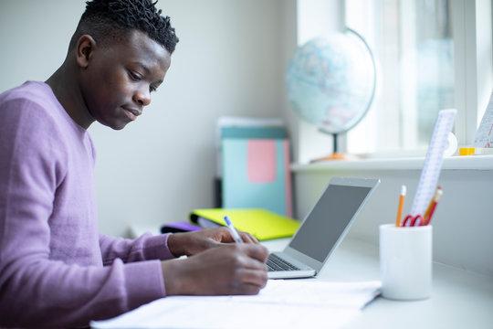 Teenage Boy Sitting At Desk Doing Homework Assignment On Laptop