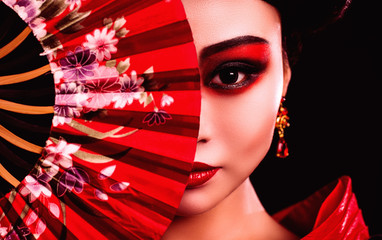 beautiful Japanese girl in kimono with a fan on a black background