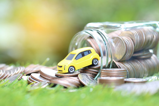 Miniature yellow car model on stack of coins money in glass bottle on nature green background, Saving money for car, Finance and car loan, Investment and business concept