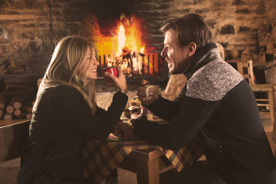 Couple drinking hot beverages in cafe in winter