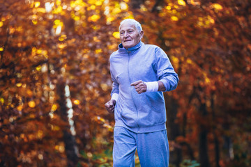 Senior runner in nature. Elderly sporty man running in forest during morning workout. Healthy and active lifestyle at any age concept
