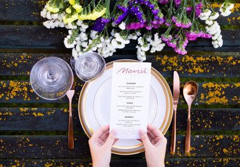 Hands Holding a Menu Mockup on Table with Tableware and Flowers