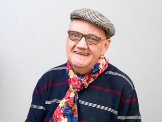 portrait vieil homme avec lunettes et béret souriant sur fond gris
