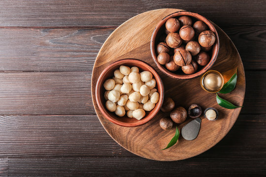 Bowls with macadamia nuts and oil on wooden table