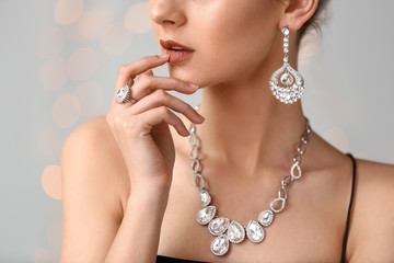 Young woman with beautiful jewelry on light background, closeup Wall mural