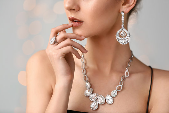 Young woman with beautiful jewelry on light background, closeup