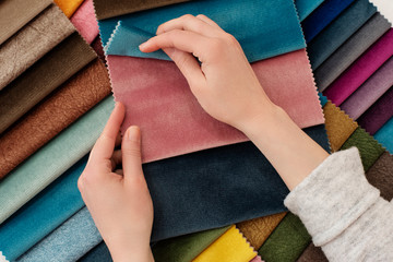 Obraz Young woman with fabric samples for curtains at table. Multiple color fabric texture samples selection fabrics for interior decoration. Furniture upholstery - fototapety do salonu