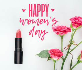 top view of lipstick and pink roses on white background with happy womens day lettering