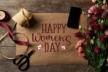 top view of ribbons, scissors, eustoma flowers, smartphone with blank screen and craft paper with happy womens day illustration on wooden background