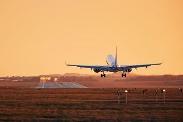 Airplane landing at sunset Wall mural