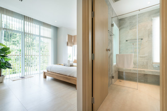Luxury Interior design in modern bedroom with hallway bathroom of pool villa with cozy king bed high raised ceiling in the  home, house , building , hotel , resort