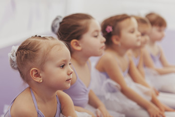 Close up of a beautiful little ballerina girl sitting with her classmates at ballet school. Group of cute little girls at dance studio. Children, kids, childhood concept