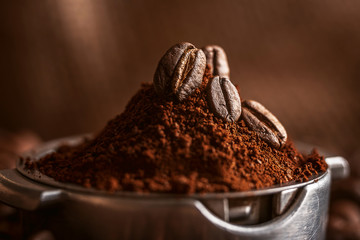 ground coffee poured into the holder on which the grains of roasted, fragrant coffee lie. on the background of fried grains