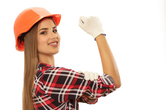 Stunning beautiful cheerful woman wearing hardhat showing we can do it sign isolated copy space. Happy young female architect or contractor flexing her biceps smiling joyfully
